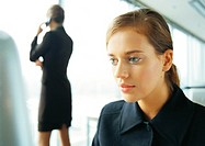 Businesswoman on cell phone, rear view, in background, blurred, businesswoman working in foreground, close-up