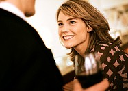 Young woman smiling at man with drink
