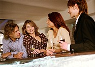 Young men and women drinking at bar