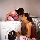 Daughter sitting on washing machine, head to head with mother