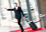 Businessman with luggage, arm extended, blurred