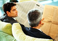 Businessmen sitting reading newspapers, rear view, head and shoulders