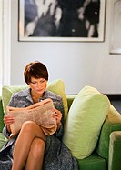 Businesswoman sitting reading newspaper