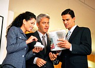 Group of business people looking at newspaper together, waist up, low angle view