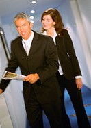 Businessman and businesswoman walking together, blurred