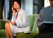 Businesswoman sitting using cell phone, man using laptop