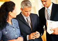 Businessmen and businesswoman, one holding cell phone