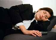 Businesswoman lying on couch, eyes closed, hand on cell phone