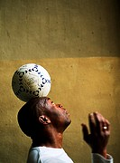 Profile view of man balancing soccer ball on head