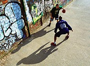 Two men playing basketball in front of graffitied wall in urban playground