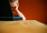 Little boy with laptop, rubbing eyes