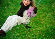 Little girl smiling on swing