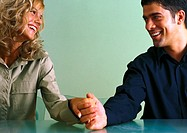 Couple holding hands at table, smiling at each other