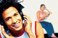 Man listening to headphones with woman in background
