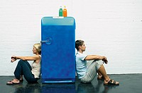 Couple seated against a fridge