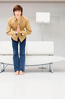 Man bowing infront of modern sofa