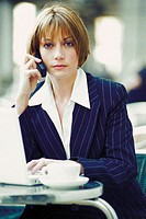 Businesswoman with laptop and cellphone at a cafe