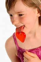 Girl licking heart shaped lollipop