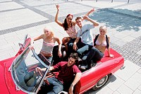 Group of young friends sitting on car