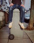 A young man sitting on a wheelie bin