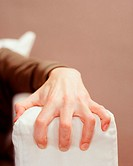 A male hand grabbing the sofa arm