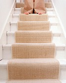 A female with bare feet coming down the stairs