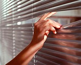 A woman peeping through venetian blinds
