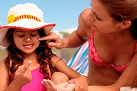 Mum putting suncream on daughter´s face
