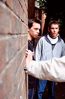 Teenage boys leaning on wall