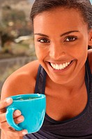 Smiling young woman with cup