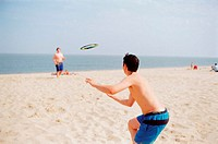 Boys playing quoits on the beach
