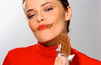 Young woman eating chocolate (thumbnail)