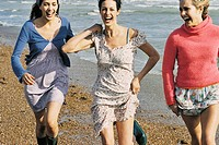 Three Laughing Women Walking on the Beach