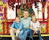 Portrait of a Man With His Two Children at An Amusement Park