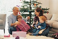 Couple Unwrapping Presents at Christmas in Front of Their Children
