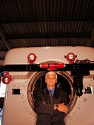 Portrait of a Mature Businessman With His Arms Crossed Standing in Front of a Machine Part in a Factory