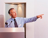 Businessman Standing Behind a Podium Looking Sideways and Pointing