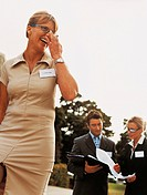 Businesswoman Laughing With Two Business Executives in the Background Reading a