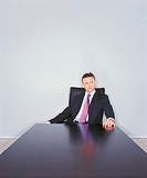 Mature Ceo Sitting at the End of a Long Table and Looking Sideways