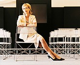 Female Ceo Sitting in a Chair in a Conference Room With Her Arms Crossed Looking Sideways
