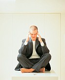 Barefoot, Young Businessman Sitting Cross Legged on top of a Table With His Eyes Closed and His Hands on His Head