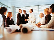 Ceo in a Conference Room Shaking Hands With a Businessman Wearing a Workcoat and Other Business People Watching