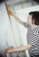 Woman stripping wallpaper (thumbnail)