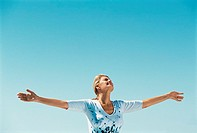 Woman standing in the sun with her arms outstretched (thumbnail)