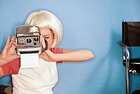 Girl using an instant camera (thumbnail)
