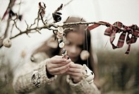 Young girl decorating a tree with buttons and shells (thumbnail)