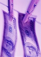 Blue duotone image of American banknotes pegged to a line (thumbnail)