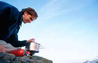 Man cooking meal on stove. Chugach State Park. Southcentral Alaska