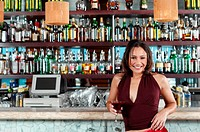 Smiling woman leaning on bar