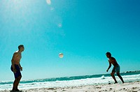 Men playing with frisbee on beach